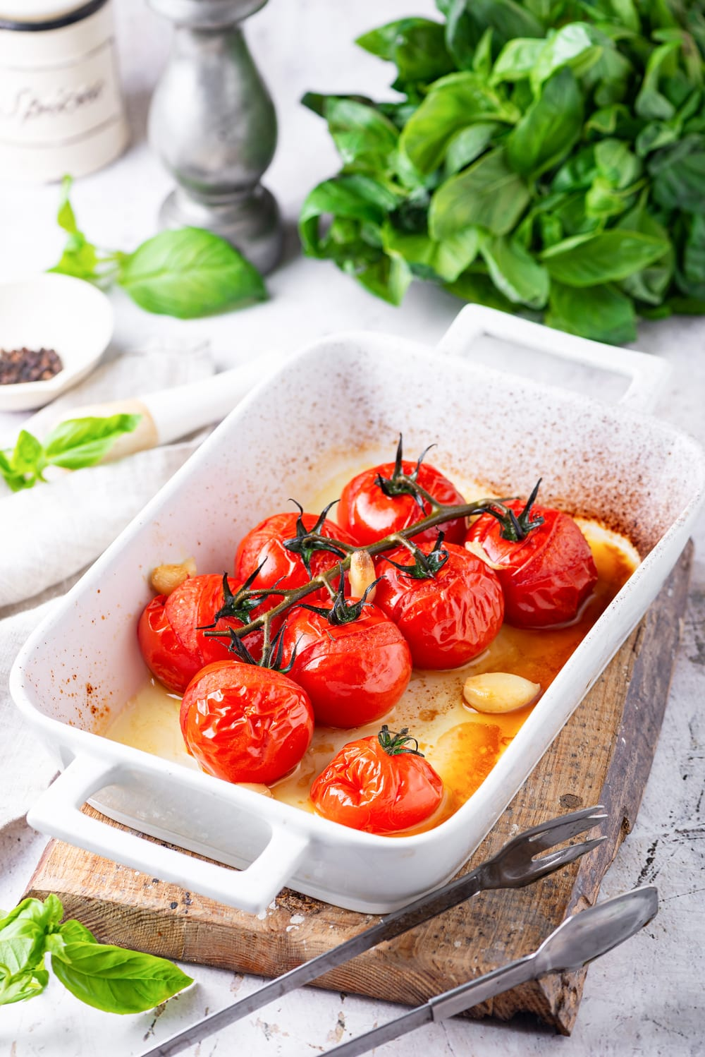 Tomatoes and garlic that have been cooked in a white baking dish with basil leaves behind it.