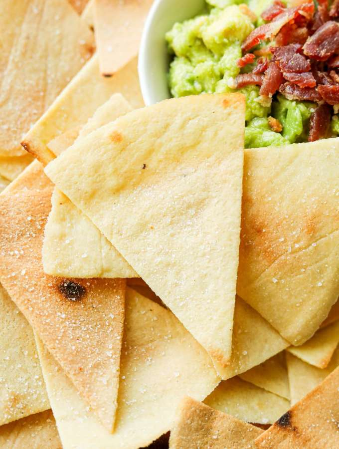 Tortilla chips pilled on top of one another next to a white bowl filled with guacamole.