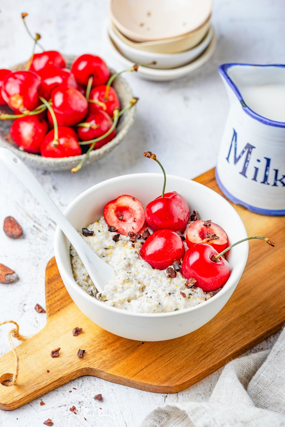 A white bowl filled with oats, bits of low carb chocolate, and cherries on a cutting board that's set on a white table.