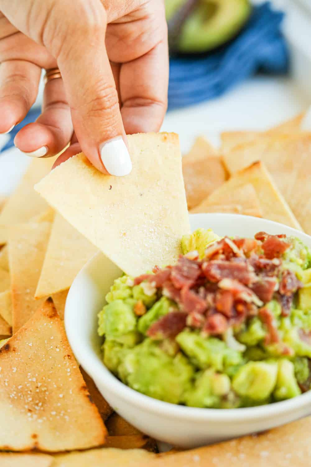 A tortilla chip being dipped into a bowl of guacamole topped with bacon.