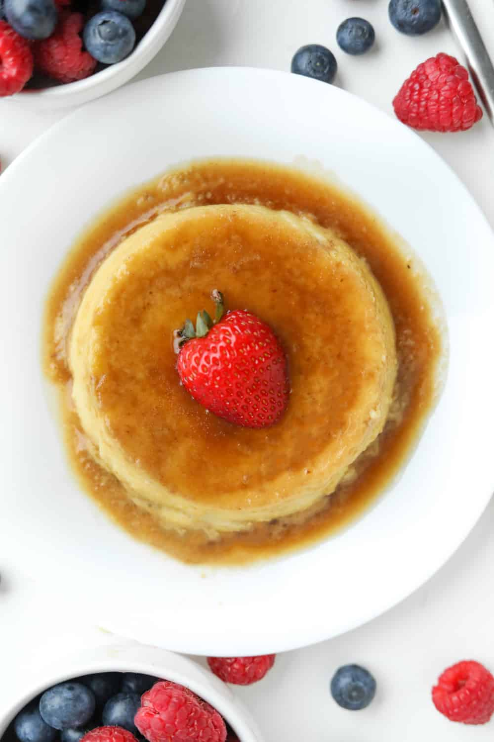 A piece of flan on a white plate set on a white table with berries all around it.