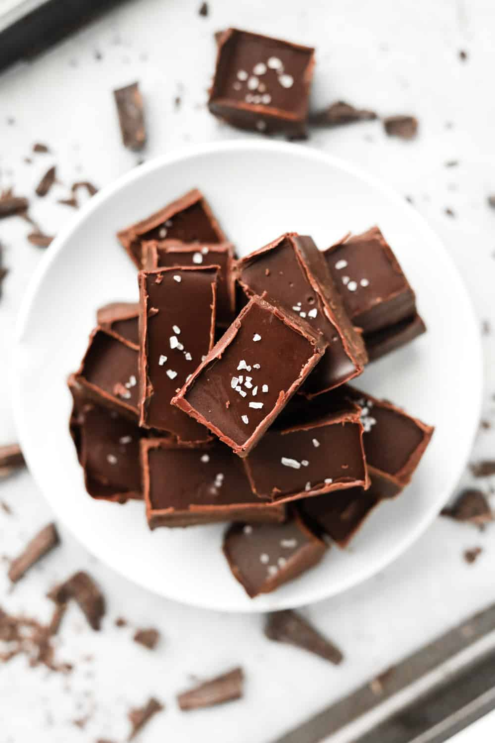 A pile of fudge on a white plate.