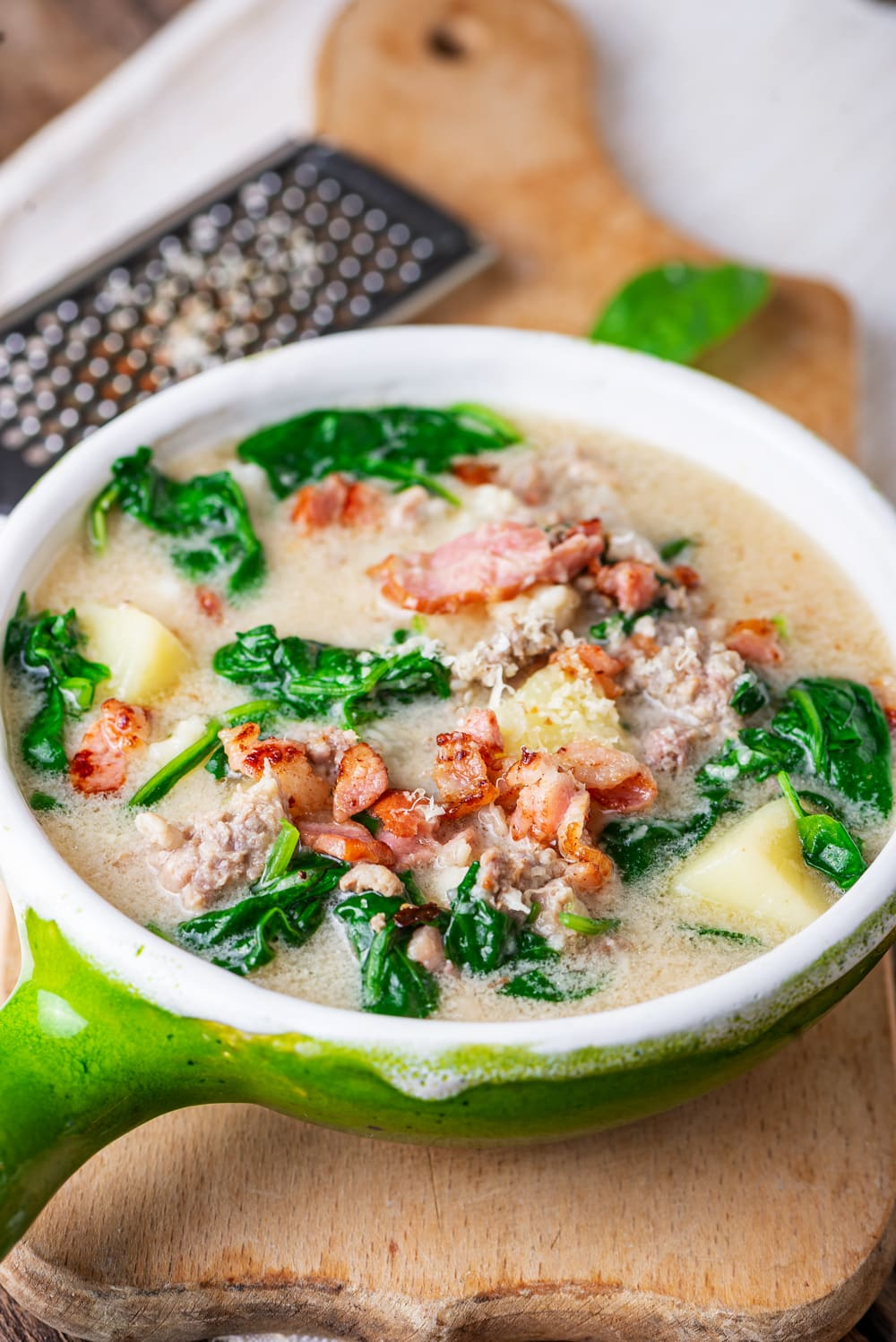 Soup with sausage, greens, and kohlrabi in a green soup bowl.