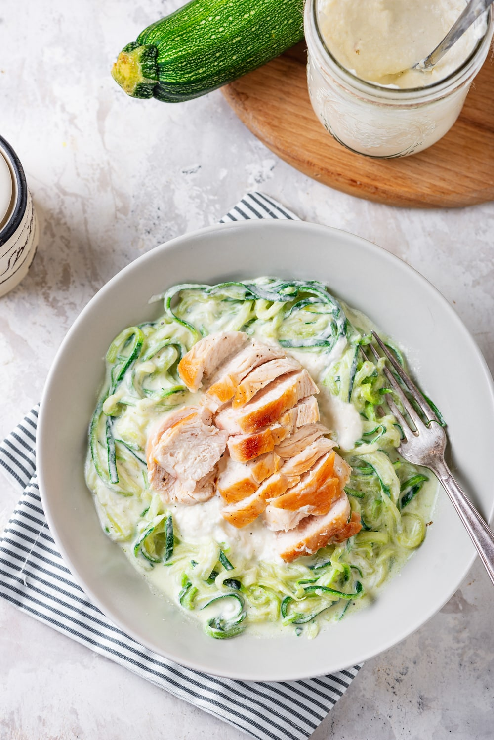 A bowl of zuchinni noodles that have been covered in alfredo sauce, and topped with a cut-up chicken breast.