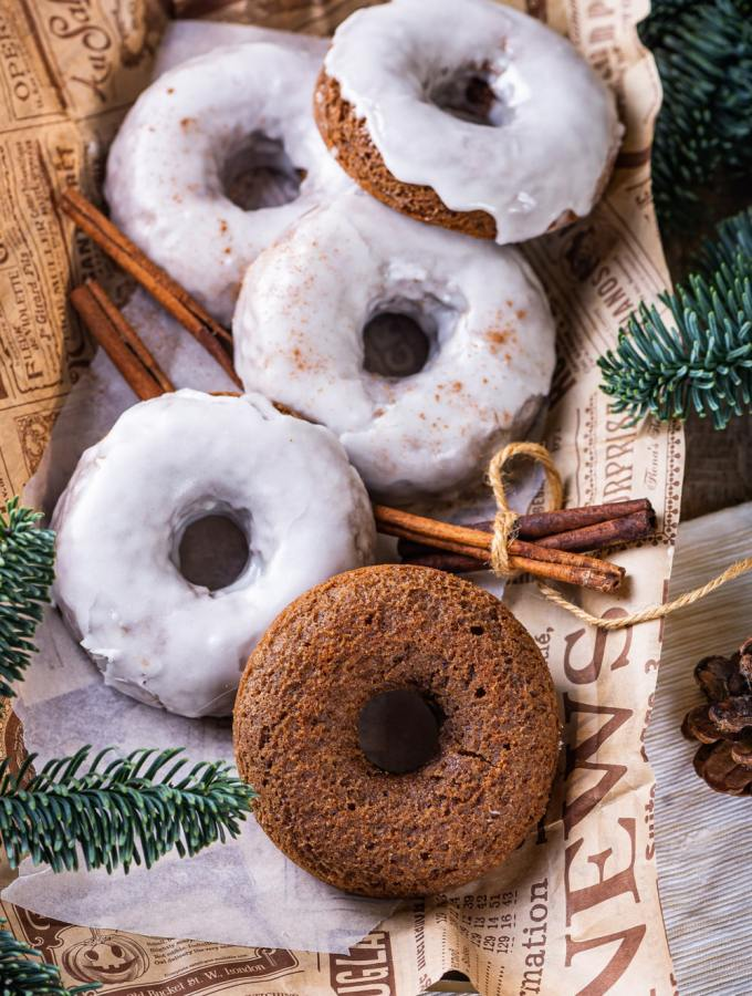 Four glazed gingerbread donuts and one plain gingerbread donut scattered on top of a piece of paper. Two sticks of cinnamon are surrounding the donuts on each side. Pine branches are at the bottom left and top right of the paper.
