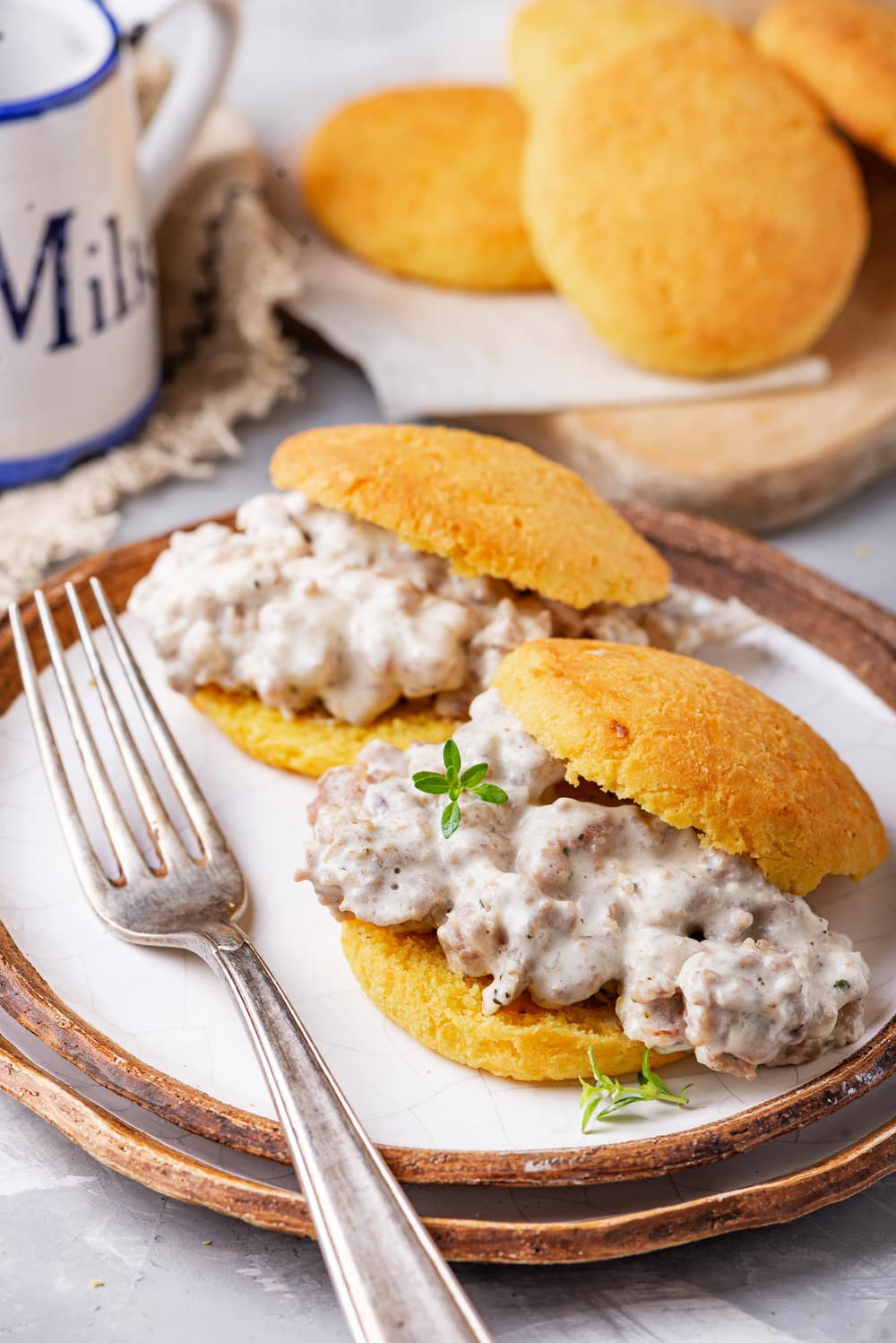 2 Biscuit and gravy sandwiches on a plate, with more biscuits behind them on a cutting board.