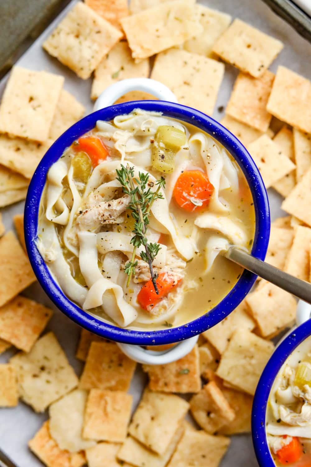 A bowl of chicken noodle soup that's surrounded by cheese crackers. There's a spoon in the bowl.