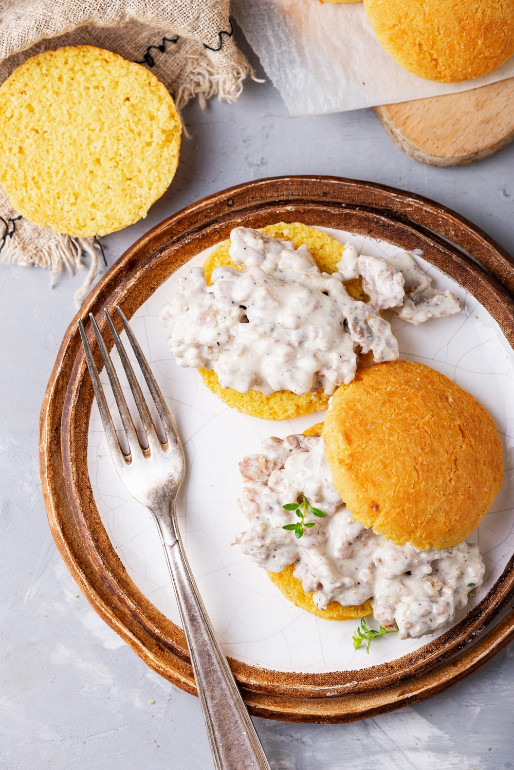 Biscuits covered in gravy on a plate. There is a fork on the plate, and more biscuits are by the plate as well.