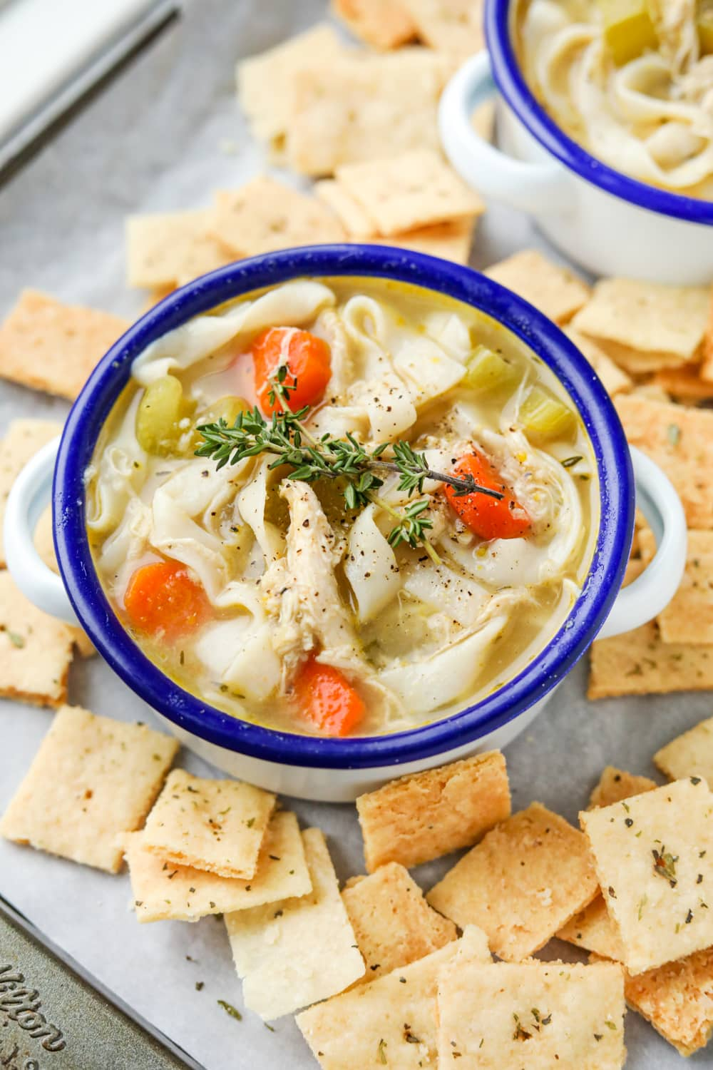 A bowl of chicken noodle soup set on a baking tray. There are crackers surrounding the soup.