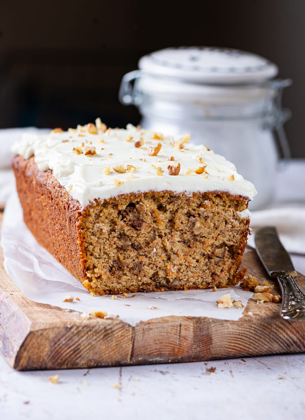 A loaf of carrot cake topped with a cream cheese frosting set on a cutting board lined with parchment paper.