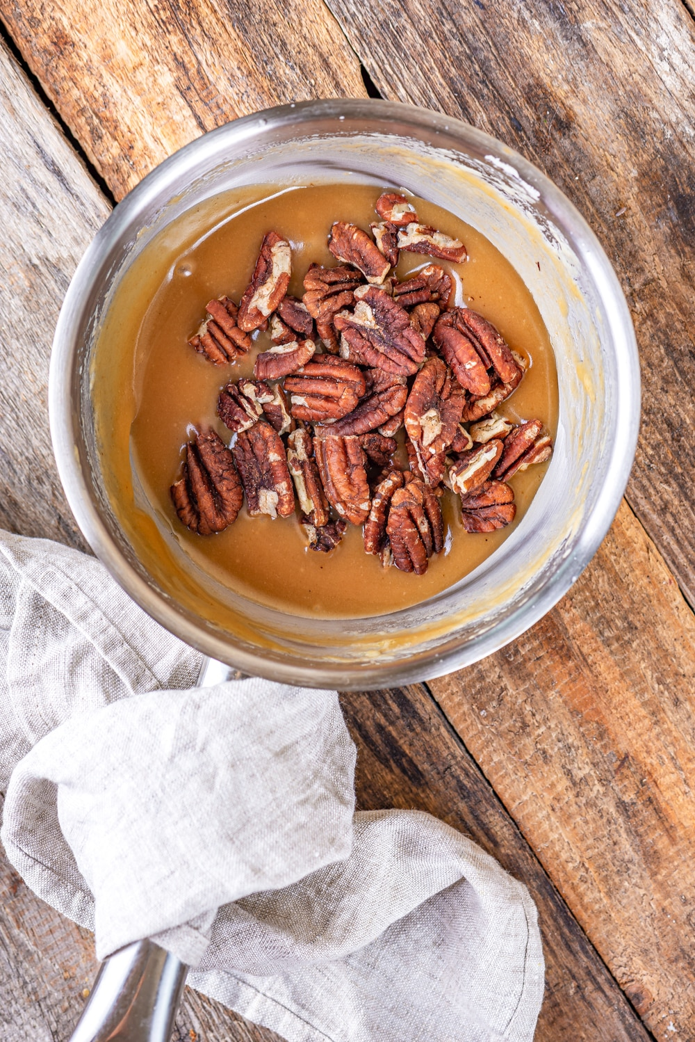 A tin pot filled with caramelized butter and pecans.