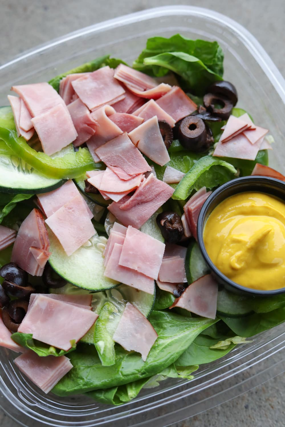 A plastic container filled with green vegetables, black olives, chopped up ham, and a cup of yellow mustard.