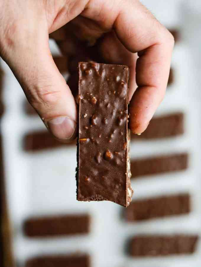 A hand holding a chocolate candy bar.