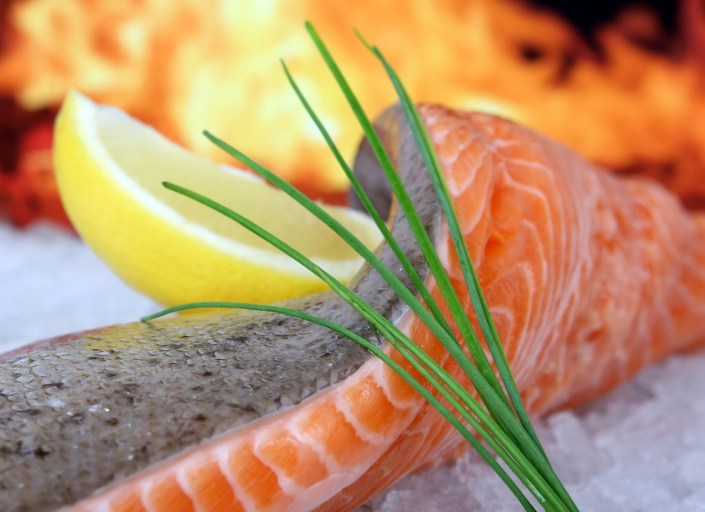 a nice salmon filet rests on ice with a lemon wedge