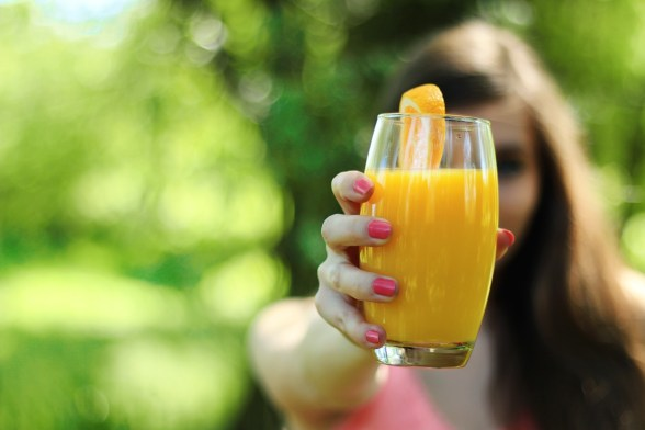 a woman holds a glass of orange juice