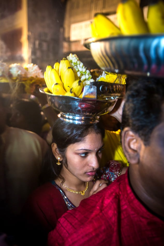 Young woman attempts to approach the chariot with her offering.
