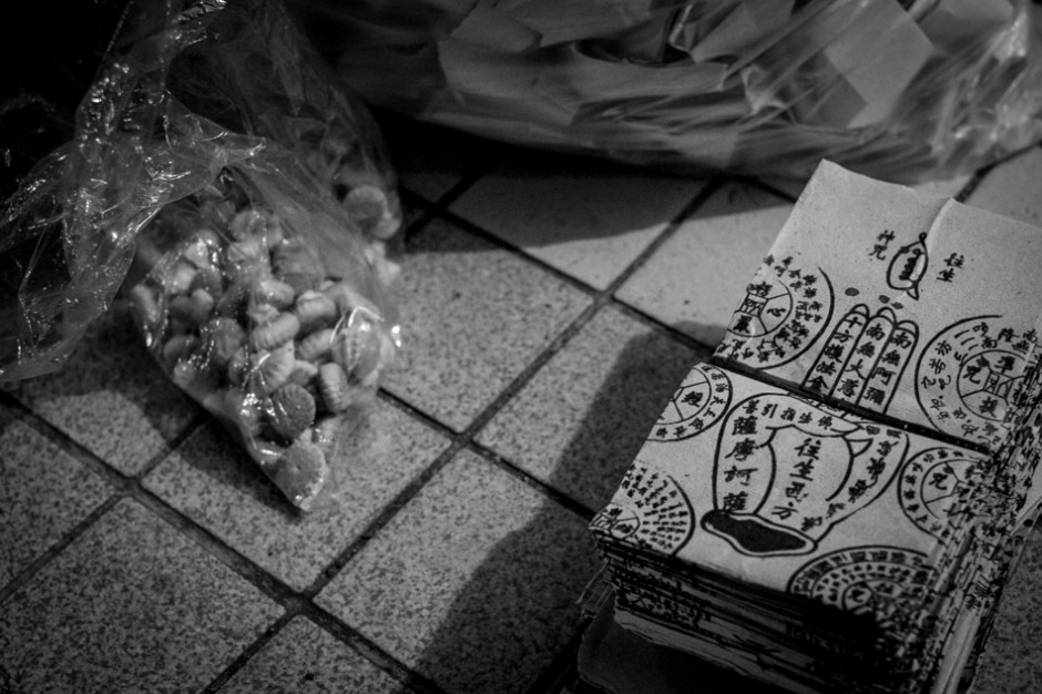 Food and a stack of paper with symbolic inscriptions ready to be burnt.f/4, 1/10 sec, at 35mm, 3200 ISO, on a X-Pro1