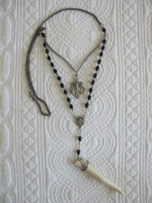 Peasant Jewelry by Michael Hickey features deconstructed rosary pieces and a bone.