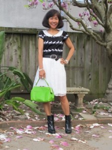 The horse t-shirt gets a polished look with a lace skirt, heeled booties, and a textured handbag.