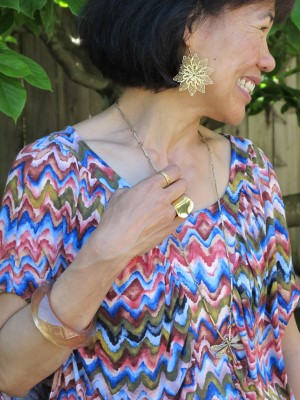 Bright fiesta colors are complemented by gold jewelry - earrings from Lava 9 in Berkeley and dragonfly necklace by Alkemie of Los Angeles. A golden smile, though, is always the strongest accessory.