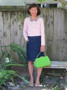 A bejeweled collar ties together a striped pink and cream casual blouse and green faux ostrich handbag.