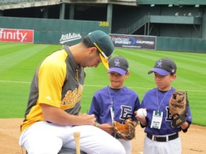 Little League Day with the Oakland A's: Geo Gonzalez signs baseballs for Jacob and his buddy and teammate Nic after participating in the pre-game Chalk Talk on the field.