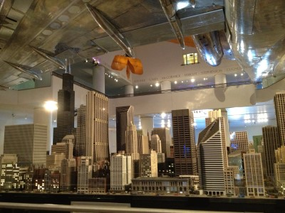 Airplanes from different time periods soar over a replica of downtown Chicago at the Museum of Science and Industry.