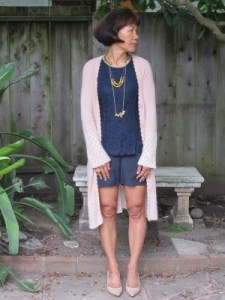 The contemplative author pose: Navy lace, silk shorts, and soft peach sweater.
