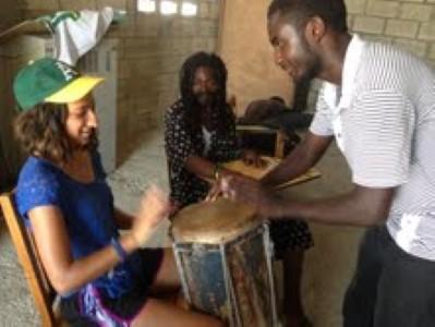 Sofia getting a Haitian drum lesson.