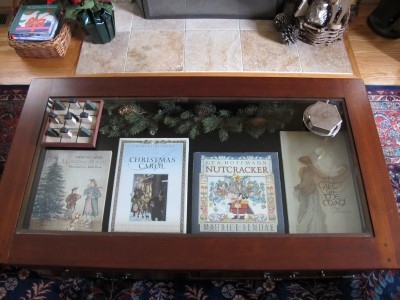My beloved coffee table displays classic holiday stories, greenery, and a snowman-tree tic-tac-toe game.