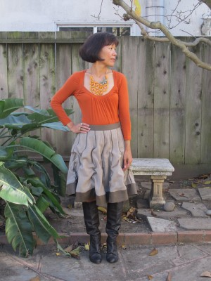 Versatile skirt with a bright orange t-shirt, baubles, and equally scrunchy heeled boots.