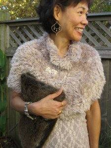 Fluffy faux fur capelet and clutch on pale pink and cream.