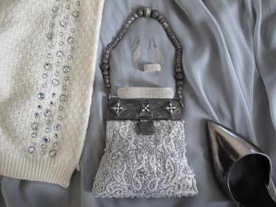 Beaded purse, Tiffany ring and bracelet, shiny silver metallic pointy pumps, and rows of gleaming gray rhinestones bejewel simple soft gray separates.