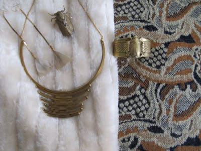 Close-up of textures and accessories: strips of creamy faux fur and muted gold, cream and navy nubby knit.