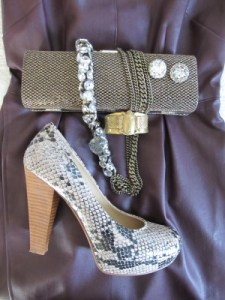 Close-up of multiple textures: vegan leather, sparkly clutch, chunky chain and stone necklace, and faux snakeskin chunky pumps.