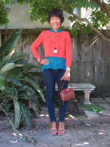 A comfortable outfit to ward off feeling overwhelmed: cropped sweater over a high-low flowing blouse, dark-rinse jeans, and platform sandals.
