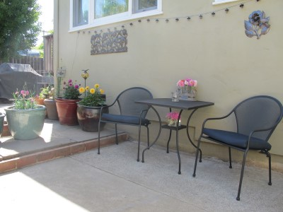 A bistro table and set of chairs find a home on the opposite side of the fence, along with potted flowers, metal sculptures and a string of solar lights.