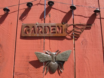 Transplanted garden sign and its new companions on the fence - a string of solar lights and a metal winged insect.