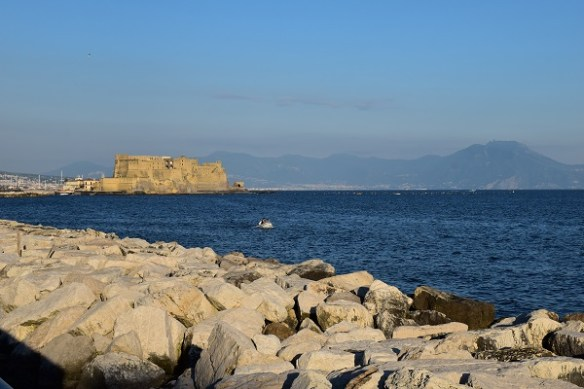 A cropping of white rocks dot the shore of Napoli, with a view of an old fort in the distance.