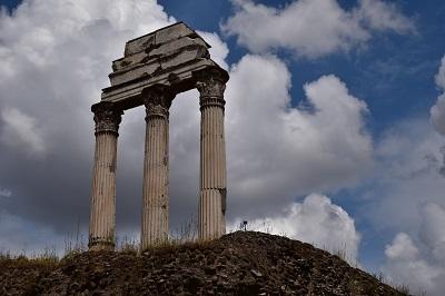 Columns facing a cloudy sky.