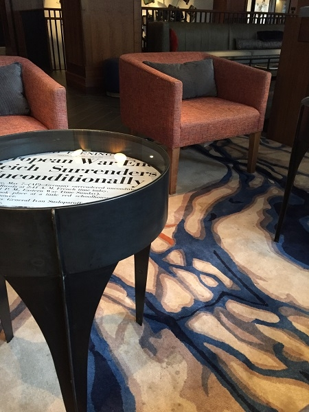 Mod Carpeting And Tables With Enlarged Old Newspaper Clippings.