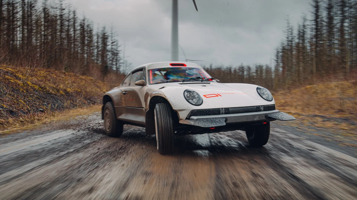Photo of the Porsche 911 redesigned by Singer Vehicle Design on the road with woods at the sides and wind generators behind.