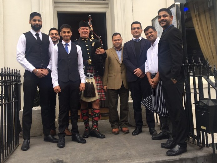 Owners of Mumbai Diners Club pose with a piper at the launch of the new restaurant