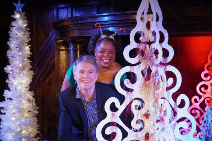 Richard Lewis seated at the piano and Andrea Baker posing with Christmas tree
