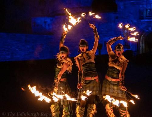 Three women with fiery hoops in front of blue castle