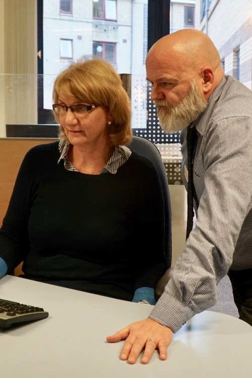 Two DWP employees in their office at a computer