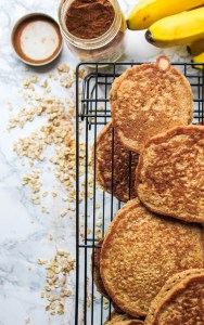 Banana Oat Pancakes stacked on a wire rack next to cinnamon and bananas