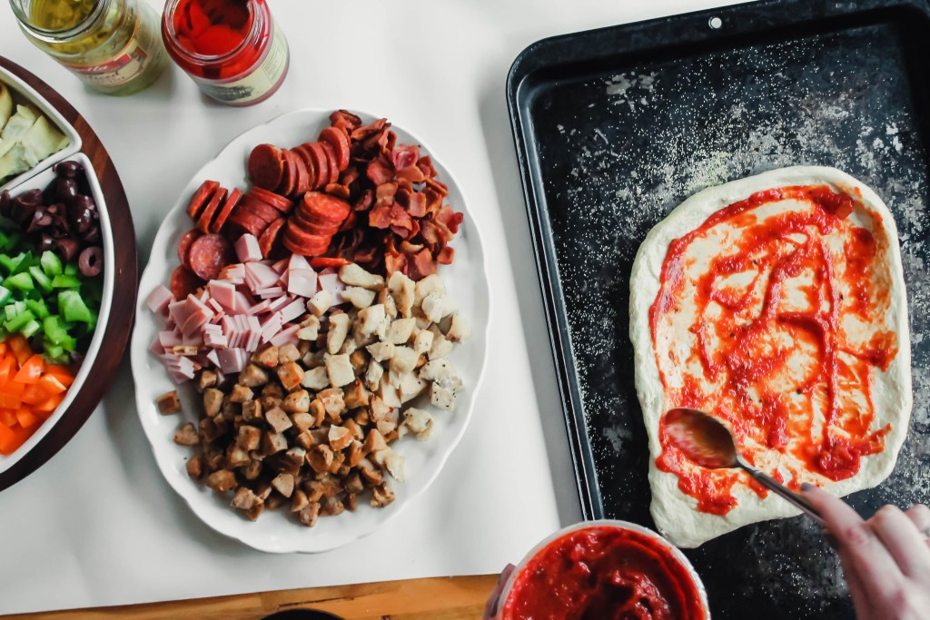 Homemade Pizza Sauce being spread on dough next to a pile of toppings