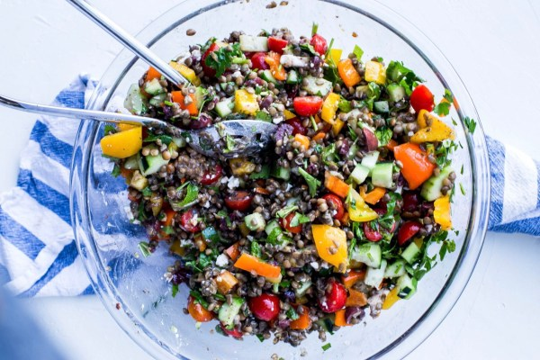 Mediteranean lentil salad mixed with bright bell peppers, tomatoes and cucumbers amongst the lentils