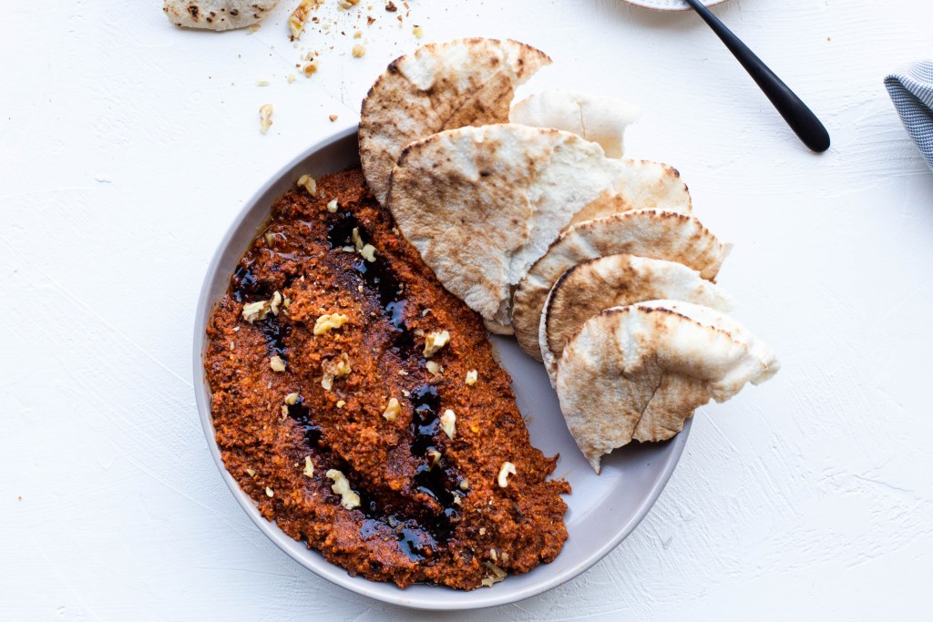 Muhammara drizzled with pomegranate molasses in a wide bowl next to torn pita bread